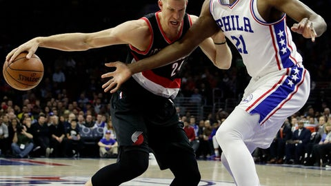 Portland Trail Blazers' Mason Plumlee, left, tries to dribble around Philadelphia 76ers' Joel Embiid during the first half of an NBA basketball game, Friday, Jan. 20, 2017, in Philadelphia. (AP Photo/Matt Slocum)