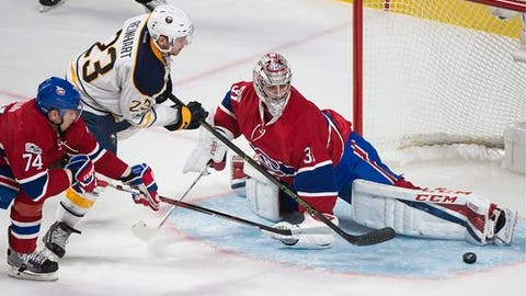 Montreal Canadiens goaltender Carey Price makes a save against Buffalo Sabres' Sam Reinhart (23) as Canadiens' Alexei Emelin (74) defends during third-period NHL hockey game action in Montreal, Saturday, Jan. 21, 2017. (Graham Hughes/The Canadian Press via AP)
