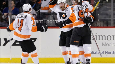 Philadelphia Flyers' Claude Giroux, second from left, celebrates with teammates after scoring the winning goal in the overtime period of the NHL hockey game against the New York Islanders, Sunday, Jan. 22, 2017, in New York. The Flyers defeated the Islanders in overtime 3-2. (AP Photo/Seth Wenig)
