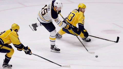 Buffalo Sabres center Jack Eichel (15) shoots from between Nashville Predators right wing James Neal (18) and left wing Colin Wilson (33) to score the winning goal during overtime at an NHL hockey game Tuesday, Jan. 24, 2017, in Nashville, Tenn. The Sabres won 5-4. (AP Photo/Mark Humphrey)