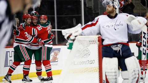New Jersey Devils players, from left, Pavel Zacha (37), of the Czech Republic, Stefan Noesen (23) and Jacob Josefson (16), of Sweden, celebrate after Noesen scored a goal on Washington Capitals goalie Braden Holtby, right, during the second period of an NHL hockey game, Thursday, Jan. 26, 2017, in Newark, N.J. (AP Photo/Julio Cortez)