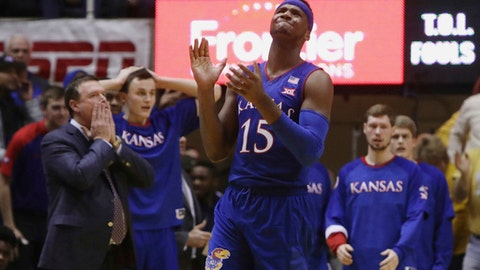 FILE - In this Jan. 24, 2017, file photo, Kansas forward Carlton Bragg Jr. (15) is disappointed by a referee's call during the second half of an NCAA college basketball game against West Virginia, in Morgantown, W.Va. At left is head coach Bill Self. Bragg has been suspended indefinitely for a violation of team rules. Coach Self said in announcing the suspension late Thursday, Jan. 26, that the violation isn't connected to an investigation into an alleged rape at his team's dorm in December. (AP Photo/Raymond Thompson)