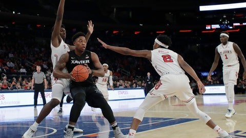 Xavier's Tyrique Jones, center, protects the ball from St. John's Darien Williams, left, and Shamorie Ponds, right, during the first half of an NCAA college basketball game, Sunday, Jan. 29, 2017, in New York. (AP Photo/Frank Franklin II)