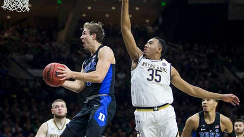 Duke's Luke Kennard, left, goes up for a layup in front of Notre Dame's Bonzie Colson (35) during the first half of an NCAA college basketball game, Monday, Jan. 30, 2017, in South Bend, Ind. (AP Photo/Robert Franklin)