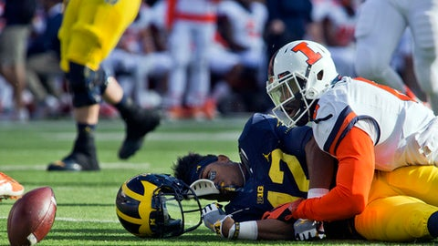 Michigan running back Chris Evans, bottom left, loses his helmet and fumbles the ball after being hit by Illinois defensive lineman Carroll Phillips, right, in the first quarter of an NCAA college football game at Michigan Stadium in Ann Arbor, Mich., Saturday, Oct. 22, 2016. Evans suffered a concussion from the play and left the game. (AP Photo/Tony Ding)