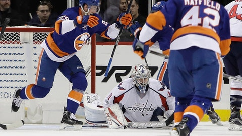 Washington Capitals goalie Philipp Grubauer (31) reacts as New York Islanders' Brock Nelson (29) and Scott Mayfield (42) celebrate a goal by Ryan Strome during the third period of an NHL hockey game Tuesday, Jan. 31, 2017, in New York. The Islanders won 3-2. (AP Photo/Frank Franklin II)