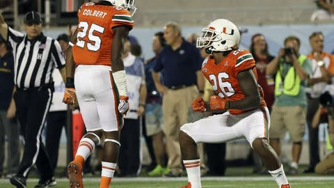 Dec 28, 2016; Orlando, FL, USA; Miami Hurricanes defensive back Rayshawn Jenkins (26) celebrates with  defensive back Adrian Colbert (25) after a play in the second half against the West Virginia Mountaineers at Camping World Stadium. The Miami Hurricanes won 31-14. Mandatory Credit: Logan Bowles-USA TODAY Sports