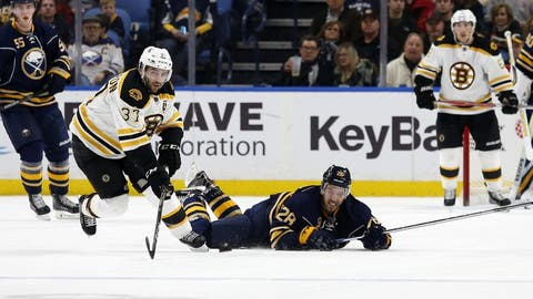 Dec 29, 2016; Buffalo, NY, USA;  Buffalo Sabres center Zemgus Girgensons (28) dives to clear the puck away from Boston Bruins center Patrice Bergeron (37) during the second period at KeyBank Center. Mandatory Credit: Timothy T. Ludwig-USA TODAY Sports