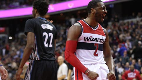 Jan 6, 2017; Washington, DC, USA; Washington Wizards guard John Wall (2) celebrates on the court in front of Minnesota Timberwolves forward Andrew Wiggins (22) in the fourth quarter at Verizon Center. The Wizards won 112-105. Mandatory Credit: Geoff Burke-USA TODAY Sports