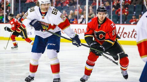 Jan 17, 2017; Calgary, Alberta, CAN; Florida Panthers right wing Jaromir Jagr (68) and Calgary Flames center Mikael Backlund (11) battle for the puck during the first period at Scotiabank Saddledome. Mandatory Credit: Sergei Belski-USA TODAY Sports