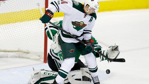 Minnesota Wild left wing Zach Parise (11) applies pressure in front of the net as Dallas Stars' Kari Lehtonen (32), of Finland, attempts to gain control of the puck in the second period of an NHL hockey game in Dallas, Saturday Jan. 14, 2017. (AP Photo/LM Otero)
