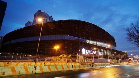 Pedestrians pass the Barclays Center before an NHL hockey game between the New York Islanders and the Washington Capitals, Tuesday, Jan. 31, 2017, in New York. (AP Photo/Frank Franklin II)