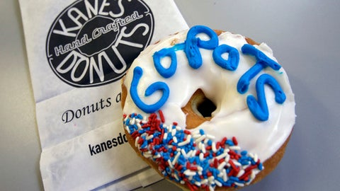 "In this Jan. 30, 2017 photo, a ""Go Pats"" donut from Kane's Donuts sits on a counter in Boston. Kane's Donuts of Saugus/Boston and Atlanta's Sublime Doughnuts are wagering a dozen of their respective handcrafted donuts on the outcome of the New England Patriots vs. Atlanta Falcons NFL Super Bowl football game on Sunday. (AP Photo/Elise Amendola)"