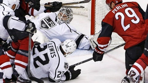 Los Angeles Kings goalie Peter Budaj, top center, makes a save on a shot by Arizona Coyotes left wing Brendan Perlini (29) as Kings center Trevor Lewis (22) defends during the third period of an NHL hockey game Tuesday, Jan. 31, 2017, in Glendale, Ariz. The Kings defeated the Coyotes 3-2. (AP Photo/Ross D. Franklin)