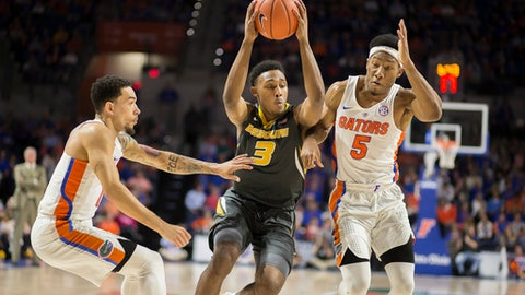 Missouri guard Frankie Hughes (3) dribbles through the defense of Florida guards Chris Chiozza, left, and KeVaughn Allen (5) during the first half of an NCAA college basketball game in Gainesville, Fla., Thursday, Feb. 2, 2017. (AP Photo/Ron Irby)