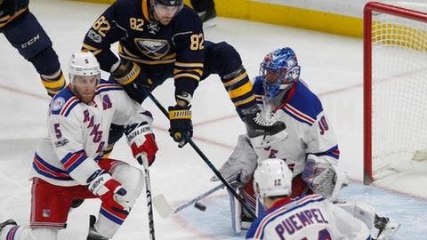 Buffalo Sabres forward Marcus Foligno (82) jumps between New York Rangers defenseman Dan Girardi (5) and goalie Henrik Lundqvist (30) during the third period of an NHL hockey game, Thursday Feb. 2, 2017, in Buffalo, N.Y. (AP Photo/Jeffrey T. Barnes)