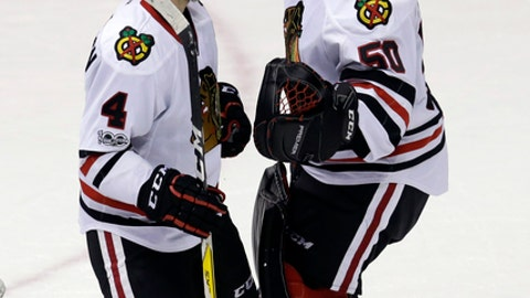 Chicago Blackhawks' Niklas Hjalmarsson (4) and Corey Crawford celebrate after the Blackhawks defeated the Arizona Coyotes during an NHL hockey game, Thursday, Feb. 2, 2017, in Glendale, Ariz. (AP Photo/Rick Scuteri)