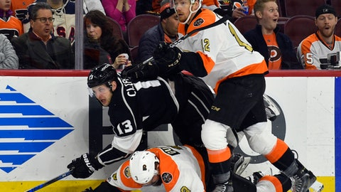 Philadelphia Flyers' Michael Raffl, right, checks Los Angeles Kings' Kyle Clifford (13) into the boards as Radko Gudas, bottom, falls to the ice during the first period of an NHL hockey game, Saturday, Feb. 4, 2017, in Philadelphia. (AP Photo/Derik Hamilton)