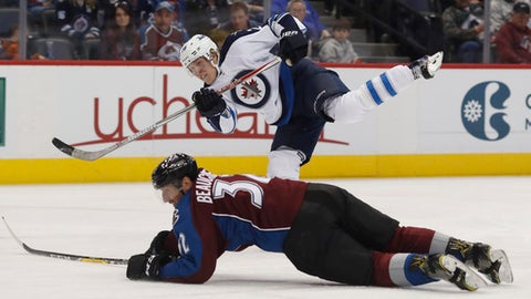 Winnipeg Jets right wing Patrik Laine, back, of Finland, follows through with his shot past Colorado Avalanche defenseman Francois Beauchemin who dives on to the ice in the second period of an NHL hockey game Saturday, Feb. 4, 2017, in Denver. (AP Photo/David Zalubowski)