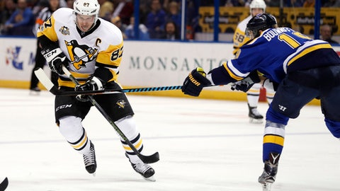 Pittsburgh Penguins' Sidney Crosby, left, chases the puck as St. Louis Blues' Jay Bouwmeester defends during the first period of an NHL hockey game Saturday, Feb. 4, 2017, in St. Louis. (AP Photo/Jeff Roberson)