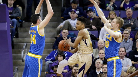 Washington's Markelle Fultz, center, leaps to pass as he drives between UCLA's Gyorgy Goloman (14) and Thomas Welsh during the second half of an NCAA college basketball game Saturday, Feb. 4, 2017, in Seattle. UCLA won 107-66. (AP Photo/Elaine Thompson)