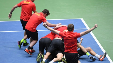 Belgian tennis players and team members celebrate after Steve Darcis won his match against Germany's Alexander Zverev in the first round Davis Cup tennis match, giving Belgium a decisive  3-1 lead , in Frankfurt, Germany, Sunday Feb. 5, 2017.  (Arne Dedert/dpa via AP)