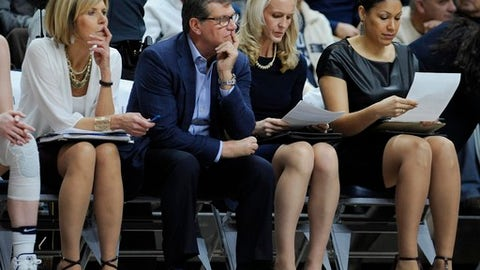 Connecticut head coach Geno Auriemma, second from left, and associate head coach Chris Dailey, left, watch play as assistant coaches Shea Ralph, and Marisa Moseley look over stat sheets during an NCAA college basketball game against Tulsa, Sunday, Feb. 5, 2017, in Storrs, Conn. (AP Photo/Jessica Hill)