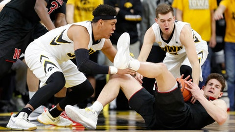 Nebraska forward Michael Jacobson, right, picks up the ball in front of Iowa's Cordell Pemsl, left, and Jordan Bohannon, rear, during the second half of an NCAA college basketball game, Sunday, Feb. 5, 2017, in Iowa City, Iowa. (AP Photo/Charlie Neibergall)