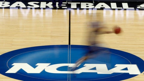 FILE - In this March 14, 2012, file photo made with a long exposure, a player runs across the NCAA logo at midcourt during practice in Pittsburgh before an NCAA tournament college basketball game.  Duke and North Carolina State were among the top 16 projected seeds the NCAA revealed Monday, Feb. 6, 2017 for the women's basketball tournament in March, making them potential hosts in a state that's lost several sports events because of a divisive law. (AP Photo/Keith Srakocic)