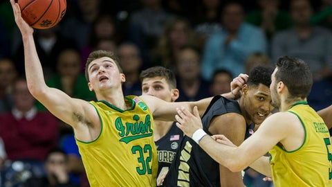 Notre Dame's Steve Vasturia (32) grabs a loose ball next to teammate Matt Farrell (5) and Wake Forest's Doral Moore, center, during the first half of an NCAA college basketball game, Tuesday, Feb. 7, 2017, in South Bend, Ind. (AP Photo/Robert Franklin)