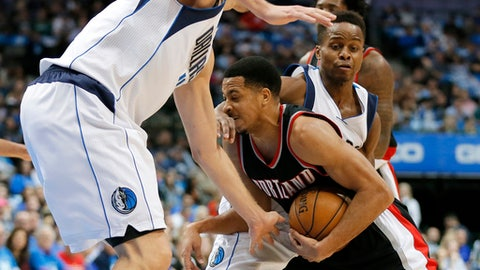 Dallas Mavericks' Dirk Nowitzki, left, of Germany and Yogi Ferrell, right, defend against a drive to the basket by Portland Trail Blazers' C.J. McCollum during the first half of an NBA basketball game in Dallas, Tuesday, Feb. 7, 2017. (AP Photo/Tony Gutierrez)