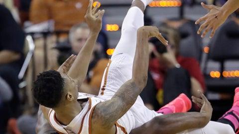 Texas guard Kerwin Roach Jr., top, passes the ball as he falls on Iowa State guard Deonte Burton (30) during the second half of an NCAA college basketball game, Tuesday, Feb. 7, 2017, in Texas, Texas. Texas won 67-65. (AP Photo/Eric Gay)