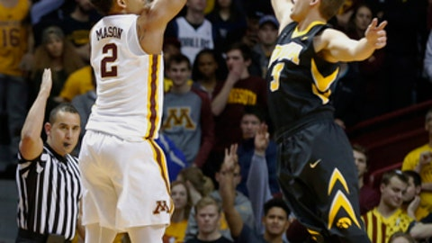 Minnesota's Nate Mason, left, shoots over Iowa's Jordan Bohannon during the first half of an NCAA college basketball game Wednesday, Feb. 8, 2017, in Minneapolis. (AP Photo/Jim Mone)