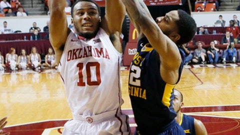 Oklahoma guard Jordan Woodard (10) shoots as West Virginia guard Tarik Phillip, right, defends during the first half of an NCAA college basketball game in Norman, Okla., Wednesday, Feb. 8, 2017. (AP Photo/Sue Ogrocki)