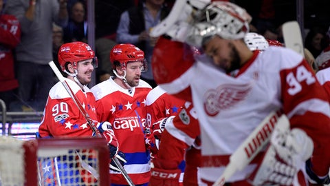 Washington Capitals left wing Marcus Johansson (90), of Sweden, celebrates his goal with Justin Williams, second from left, as Detroit Red Wings goalie Petr Mrazek (34), of the Czech Republic, looks on during the first period of an NHL hockey game, Thursday, Feb. 9, 2017, in Washington. (AP Photo/Nick Wass)