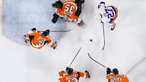 New York Islanders' Anders Lee (27) tries to get a shot past Philadelphia Flyers' Steve Mason (35), Radko Gudas (3), Roman Lyubimov (13) and Chris VandeVelde (76) during the third period of an NHL hockey game, Thursday, Feb. 9, 2017, in Philadelphia. (AP Photo/Matt Slocum)