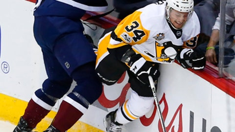 Colorado Avalanche defenseman Nikita Zadorov (16) checks Pittsburgh Penguins right wing Tom Kuhnhackl (34) against the boards during the first period of an NHL hockey game, Thursday, Feb. 9, 2017, in Denver. (AP Photo/Jack Dempsey)