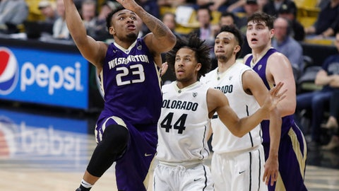 From left, Washington guard Carlos Johnson drives the lane to the rim as Colorado guards Josh Fortune and Derrick White and Washington forward Sam Timmins look on in the first half of an NCAA college basketball game Thursday, Feb. 9, 2017, in Boulder, Colo. (AP Photo/David Zalubowski)