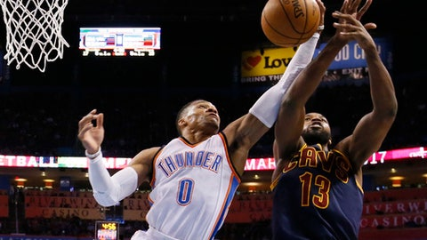Oklahoma City Thunder guard Russell Westbrook (0) grabs a rebound in front of Cleveland Cavaliers center Tristan Thompson (13) during the first quarter of an NBA basketball game in Oklahoma City, Thursday, Feb. 9, 2017. (AP Photo/Sue Ogrocki)
