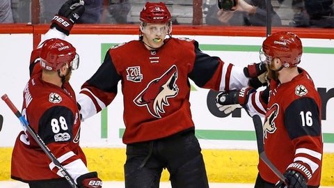 Arizona Coyotes center Christian Dvorak (18) celebrates his goal against the Montreal Canadiens with left wing Max Domi (16) and left wing Jamie McGinn (88) during the second period of an NHL hockey game Thursday, Feb. 9, 2017, in Glendale, Ariz. (AP Photo/Ross D. Franklin)