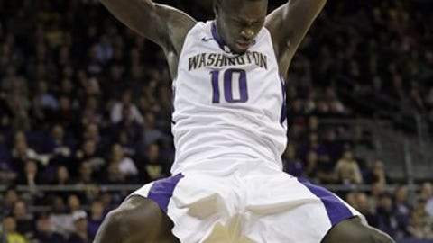 Washington's Malik Dime hangs on the rim after dunking against Oregon in the second half of an NCAA college basketball game Wednesday, Jan. 4, 2017, in Seattle. Oregon won 83-61. (AP Photo/Elaine Thompson)