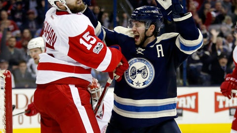 Columbus Blue Jackets forward Boone Jenner, right, celebrates in front of Detroit Red Wings forward Riley Sheahan after Blue Jackets forward Cam Atkinson scored during the second period of an NHL hockey game in Columbus, Ohio, Saturday, Feb. 11, 2017. (AP Photo/Paul Vernon)