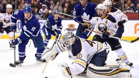 Buffalo Sabres goalie Robin Lehner (40) covers up the puck as defenseman Josh Gorges (4) defends and Toronto Maple Leafs left wing Matt Martin (15) looks for a rebound during second period NHL hockey action in Toronto on Saturday, Feb. 11, 2017. (Frank Gunn/The Canadian Press via AP)