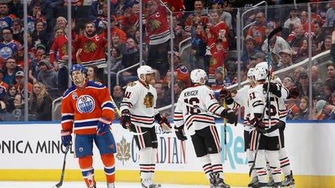 Chicago Blackhawks celebrate a goal as Edmonton Oilers center Anton Lander (51) skates to the bench during the second period of an NHL hockey game Saturday, Feb. 11, 2017, in Edmonton, Alberta. (Jason Franson/The Canadian Press via AP)