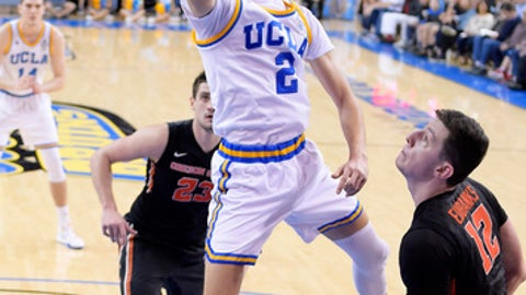 UCLA guard Lonzo Ball, center, shoots as Oregon State center Gligorije Rakocevic, left, and forward Drew Eubanks defend during the first half of an NCAA college basketball game, Sunday, Feb. 12, 2017, in Los Angeles. (AP Photo/Mark J. Terrill)