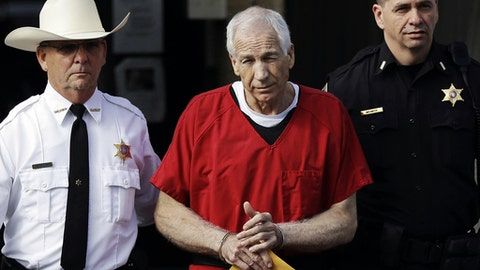 FILE - In this Oct. 9, 2012, file photo, former Penn State assistant football coach Jerry Sandusky, center, is taken from the Centre County Courthouse by Centre County Sheriff Denny Nau, left, and a deputy, after being sentenced in Bellefonte, Pa. A judge on Wednesday, Oct. 28, 2015, ordered prosecutors to take another look at a man's allegations that Sandusky molested him as a teenager. (AP Photo/Matt Rourke, File)