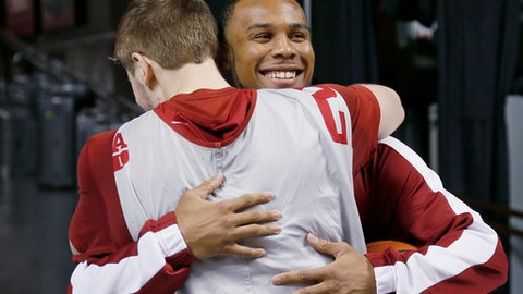 Oklahoma point guard Jordan Woodard, right, is hugged by teammate Daniel Harper, left, as he arrives for a news conference in Norman, Okla., Monday, Feb. 13, 2017. Woodard is out for the season with a torn ACL in his right knee, effectively ending his college career. (AP Photo/Sue Ogrocki)
