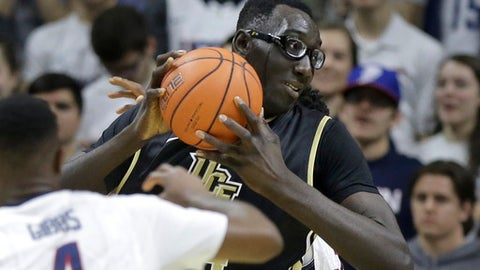 In this Sunday, March 6, 2016, photo, Central Florida's Tacko Fall, center, tries to drive toward the basket past Connecticut's Sterling Gibbs (4) in the second half of an NCAA college basketball game in Storrs, Conn. UCF got off to a 7-1 start and was receiving Top 25 votes but it wasn't long before some of the challenges of the makeup of the team started to set in. Senior guard Matt Williams, sophomore guard B.J. Taylor and Fall are quality players, but with just seven scholarship players the Knights have found it difficult to stay in games due to their lack of depth. (AP Photo/Steven Senne)