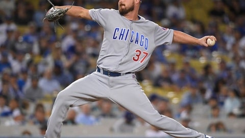FILE- This Oct. 19, 2016 file photo shows Chicago Cubs relief pitcher Travis Wood throwing during the seventh inning of Game 4 of the National League baseball championship series against the Los Angeles Dodgers in Los Angeles. A person familiar with the deal says the Kansas City Royals and left-hander Travis Wood have agreed to a $12 million, two-year contract. The person spoke to The Associated Press on condition of anonymity Monday, Feb. 13, 2017 because the deal is pending a physical. (AP Photo/Mark J. Terrill)