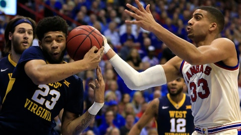 West Virginia forward Esa Ahmad (23) rebids against Kansas forward Landen Lucas (33) during the first half of an NCAA college basketball game in Lawrence, Kan., Monday, Feb. 13, 2017. (AP Photo/Orlin Wagner)